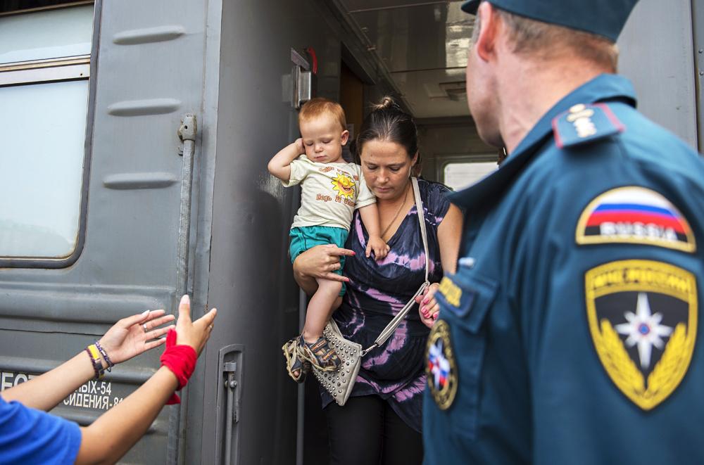Alcuni volontari accolgono rifugiati ucraini alla stazione dei treni di Omsk.