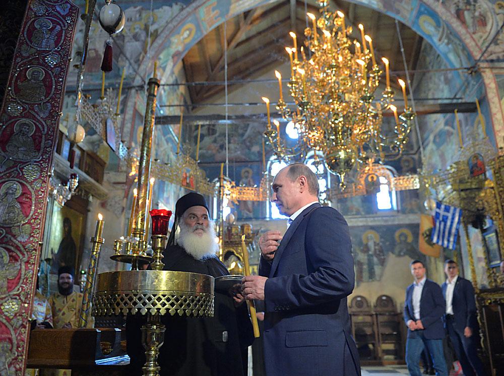 Pútin (centro) acende vela na igreja de Protaton, em Karyes, o centro administrativo da comunidade ortodoxa do Monte Athos, na Grécia.