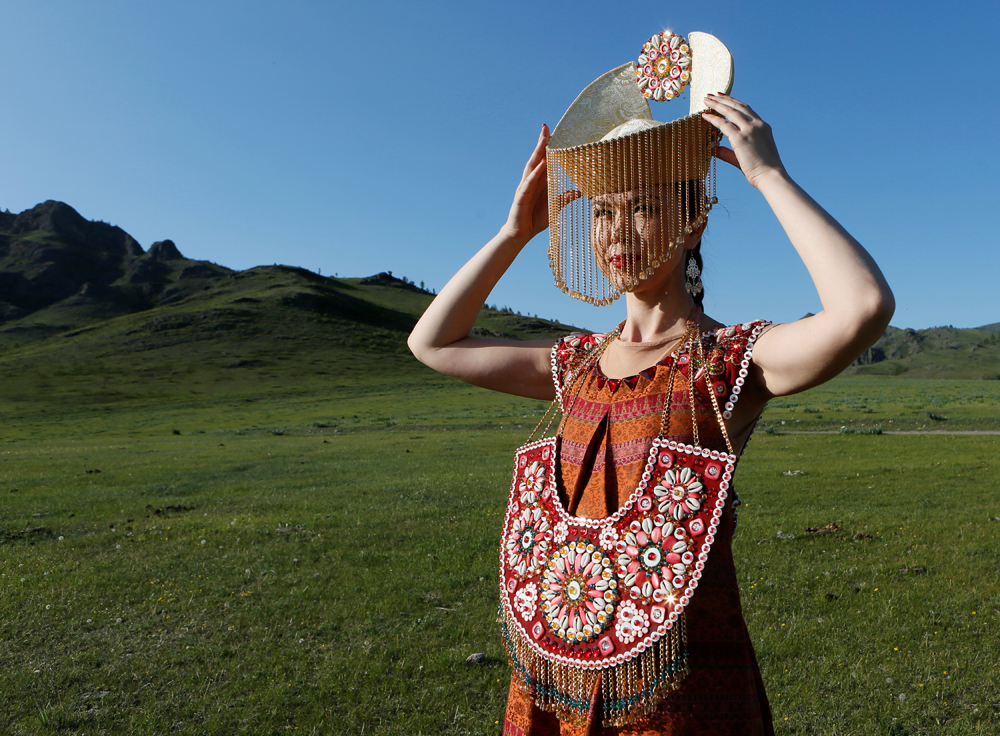 "A model of the ""Altyr"" fashion theatre, dressed in a Khakas national costume, poses during a photo session, as a part of the rehearsal for the Tun-Pairam traditional holiday (The Holiday of the First Milk) celebration at a museum preserve outside Kazanovka village near Abakan in the Republic of Khakassia, Russia, May 28, 2016. The museum preserve is located in a picturesque forest-steppe valley near the Abakan ridge of the Kuznetsk Alatau mountain range and displays numerous objects of the cultural and historical heritage of various epochs accumulated by the people living on this territory, according to representatives"