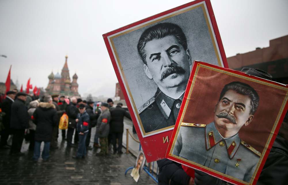 A man holds portraits of Josef Stalin before laying flowers at the grave of the Soviet leader during a ceremony to mark the 61th anniversary of Stalin's death in the Red Square in Moscow, March 2014.