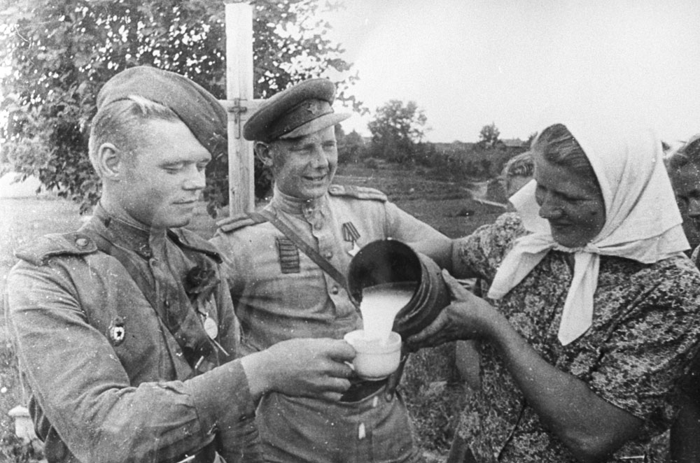 1944.  Riga (now Latvia). A woman treats Red Army soldiers to a jug of milk.