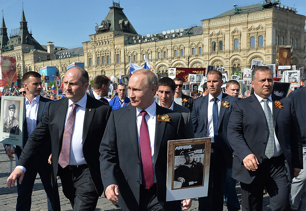 Vladimir Putin holds a portrait of his father Vladimir Spiridonovich Putin who fought in World War II during the Immortal Regiment march in Moscow, May 9, 2016. Source: Alexei Druzhinin/Russian Presidential Press and Information Office/TASS