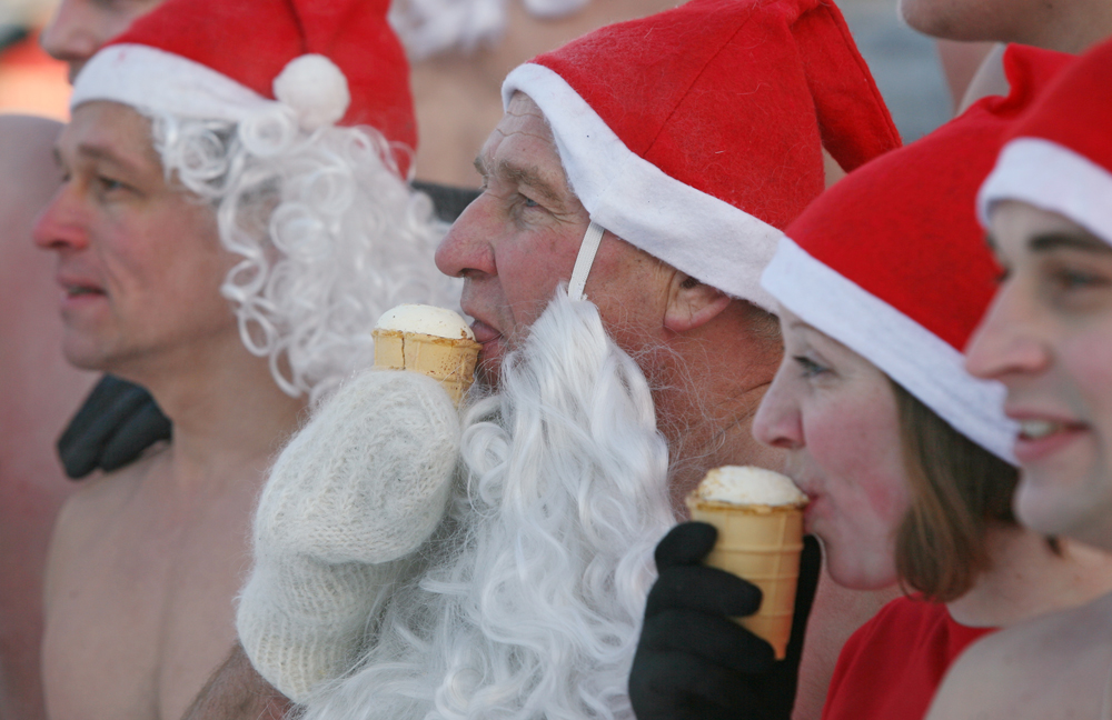 Members of the Spektr cold training club and Polar Dolphins winter swimming federation, dressed as Father Frosts, eating ice-cream during their New Year race in Novosibirsk.