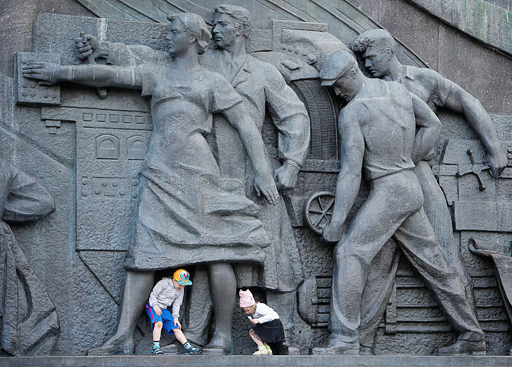 Children play near the Monument to the Conquerors of Space in Moscow, Russia