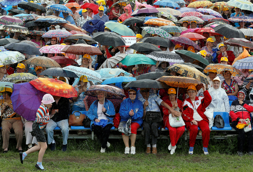 Spectators attend the 'Festival of Possibilities', an annual sports, fitness and dancing event for people aged over 55, as it rains in the Siberian city of Krasnoyarsk, Russia
