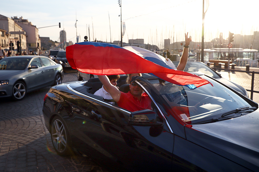 Russian football fans hold a flag as they drive in Marseille ahead of the England v Russia game on Saturday, on June 9, 2016 in Marseille, France. Football fans from around Europe have descended on France for the UEFA Euro 2016 football tournament.