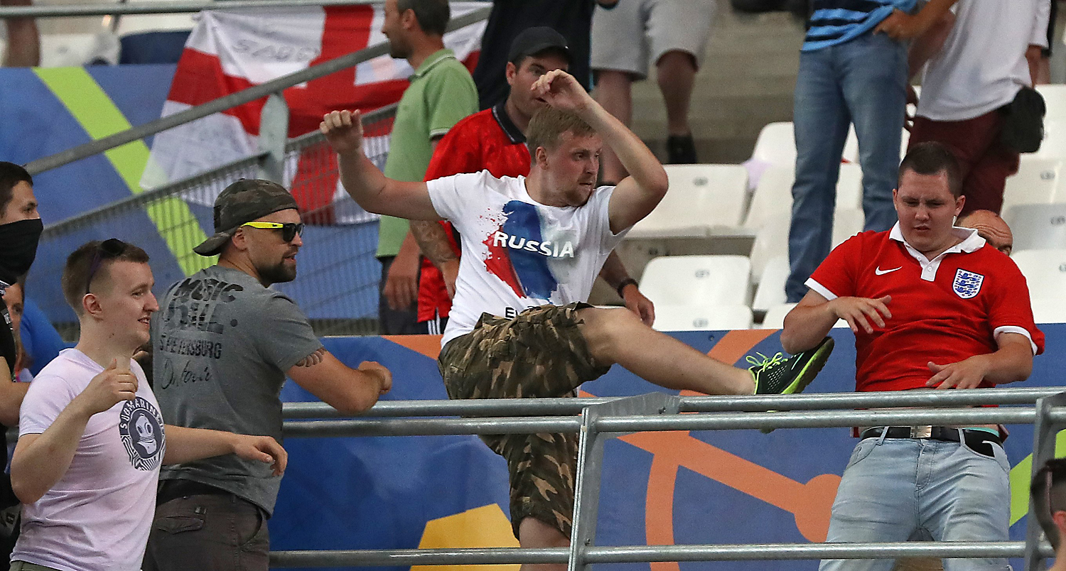 June 11, 2016 file photo, Russian supporters attack an England fan at the end of the Euro 2016 Group B soccer match between England and Russia, at the Velodrome stadium in Marseille, France. UEFA's disciplinary body says Tuesday, June 14, 2016 Russia will be disqualified from the European Championship if there is more fan violence inside stadiums in France.