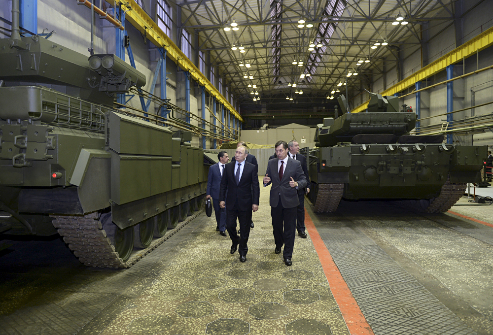 Russian President Vladimir Putin (L) listens to Andrei Terlikov, the head of the Ural Transport Machine Building Design Bureau, as they watch Russian infantry fighting vehicle with the Armata Universal Combat Platform and a T-14 Armata main battle tank at he Uralvagonzavod factory in the Urals city of Nizhny Tagil, Russia November 25, 2015.