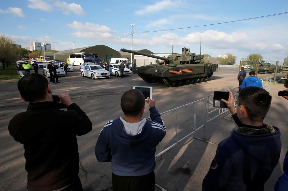 Orang-orang mengambil foto tank T-14 dengan platform tempur universal Armata saat kendaraan lapis baja ini meninggalkan medan militer untuk ikut dalam latihan parade Hari Kemenangan di Moskow, Rusia, 5 Mei 2016.