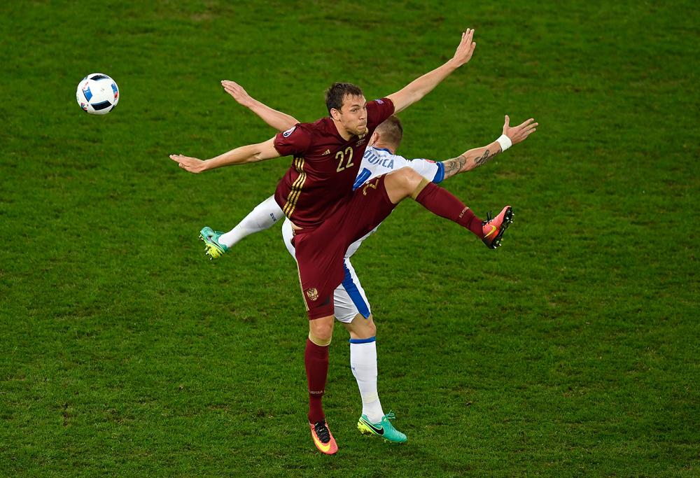 Das ganze Spiel in nur einem Bild: Jan Durica aus der slowakischen Nationalelf tänzelt mit dem russischen Stürmer Artjom Dzjuba um den Ball bei der Fußball-EM 2016 in Frankreich.