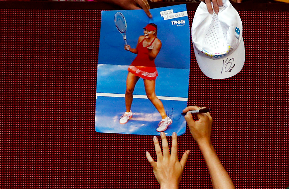 Russia's Maria Sharapova signs autographs after winning her third round match against Lauren Davis of the U.S. at the Australian Open tennis tournament at Melbourne Park, Australia, January 22, 2016.
