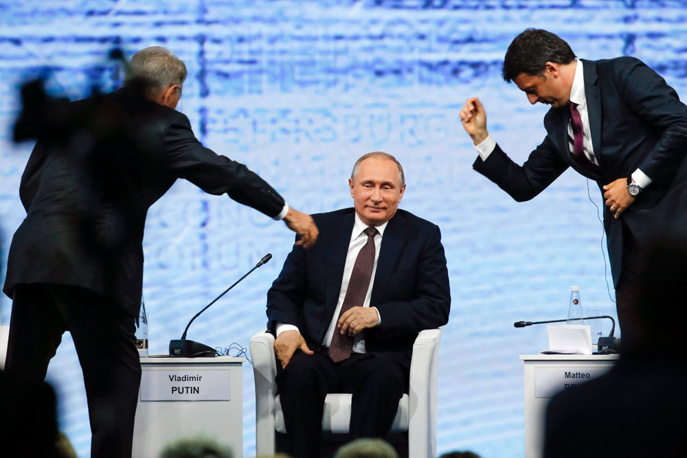 Italian Premier Matteo Renzi, right, and Kazakhstan's President Nursultan Nazarbayev reach out to shake hands as Russian President Vladimir Putin, center, looks on, at the St. Petersburg International Economic Forum in St. Petersburg, Russia, Friday, June 17, 2016. Russian President Vladimir Putin has called on European leaders to improve ties with his country despite sanctions.