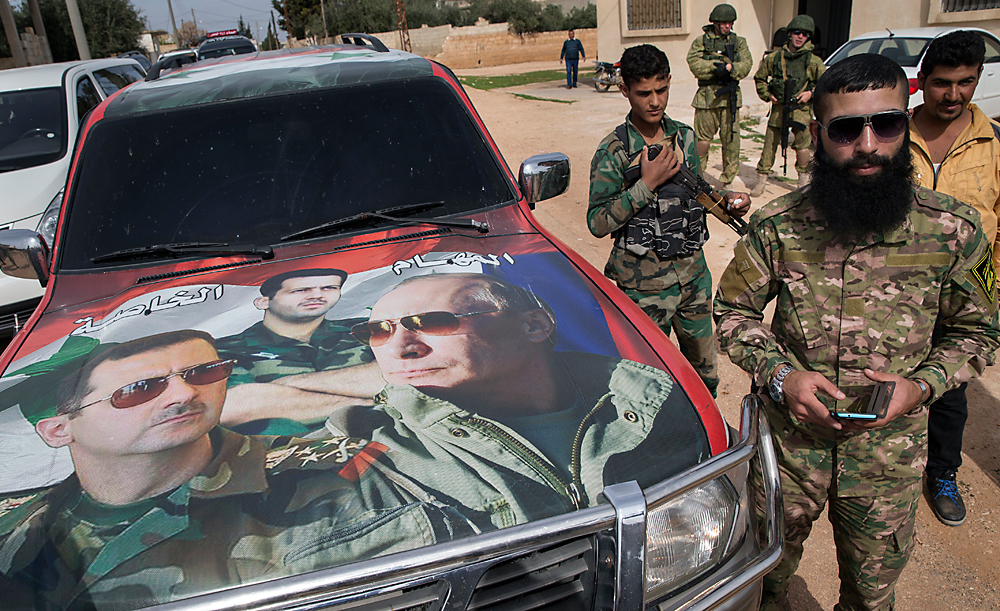 Syrian and Russian solders, who escort a group of journalists in the background, stand near a car covered by collage showing photos of faces of Russian President Vladimir Putin, Syrian President Bashar Assad and a Syrian general, President's Assad brother, Maher Assad, center, in Maarzaf, about 15 kilometers west of Hama, Syria, March 2, 2016.