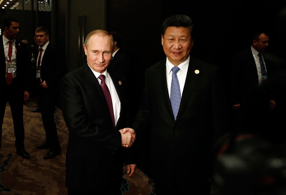 In this Sunday, Nov. 15, 2015 photo, Russian President Vladimir Putin, left, shakes hand with Chinese President Xi Jinping, right, prior to their meeting at the G-20 Summit in Antalya, Turkey. The leaders of the Group of 20 were wrapping up their two-day summit in Turkey Monday against the backdrop of heavy French bombardment of the Islamic State's stronghold in Syria. The bombings marked a significant escalation of France's role in the fight against the extremist group.