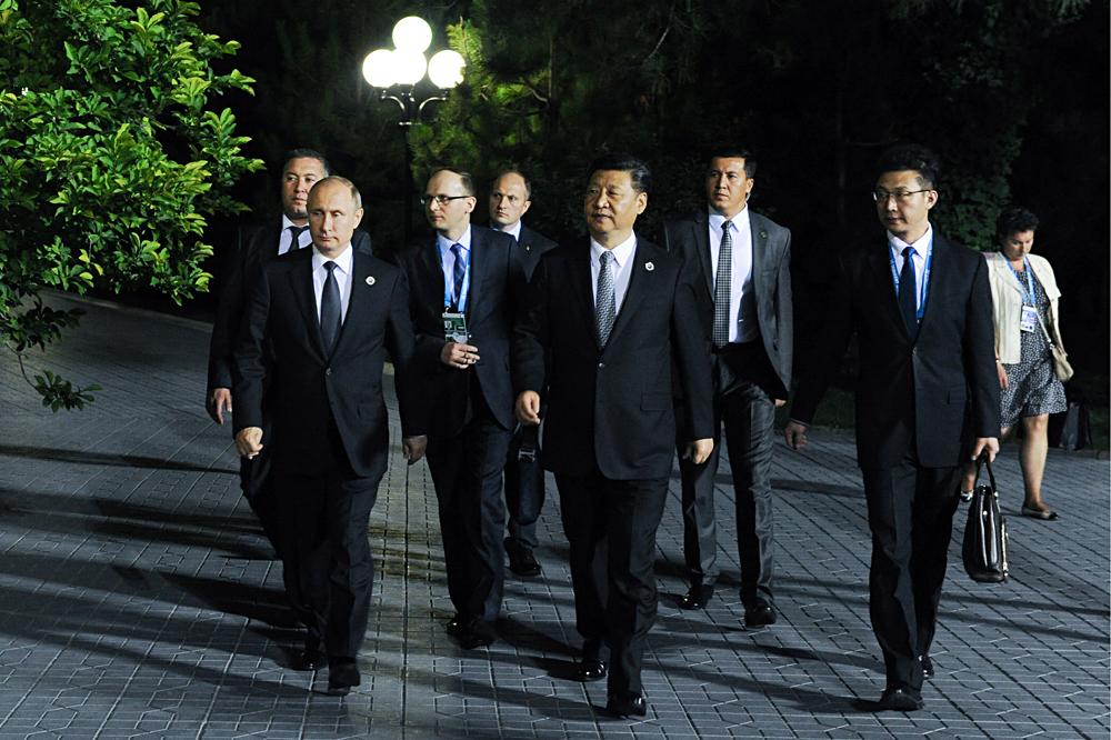 Russia's president Vladimir Putin (L), and China's president Xi Jinping (C) during a meeting in Tashkent.