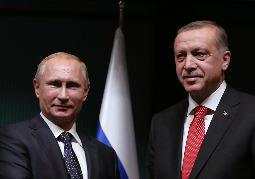 Russian President Vladimir Putin, left, and his Turkish counterpart Recep Tayyip Erdogan shake hands after a joint news conference at the new Presidential Palace in Ankara, December 1, 2014.