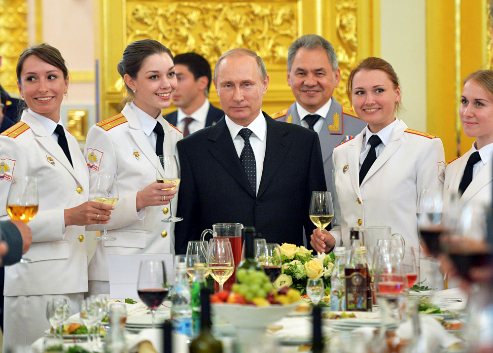 Russian President Vladimir Putin (C) and Defence Minister Sergei Shoigu (back) attend a reception to honour graduates of military academies at the Kremlin in Moscow, Russia, June 28, 2016.