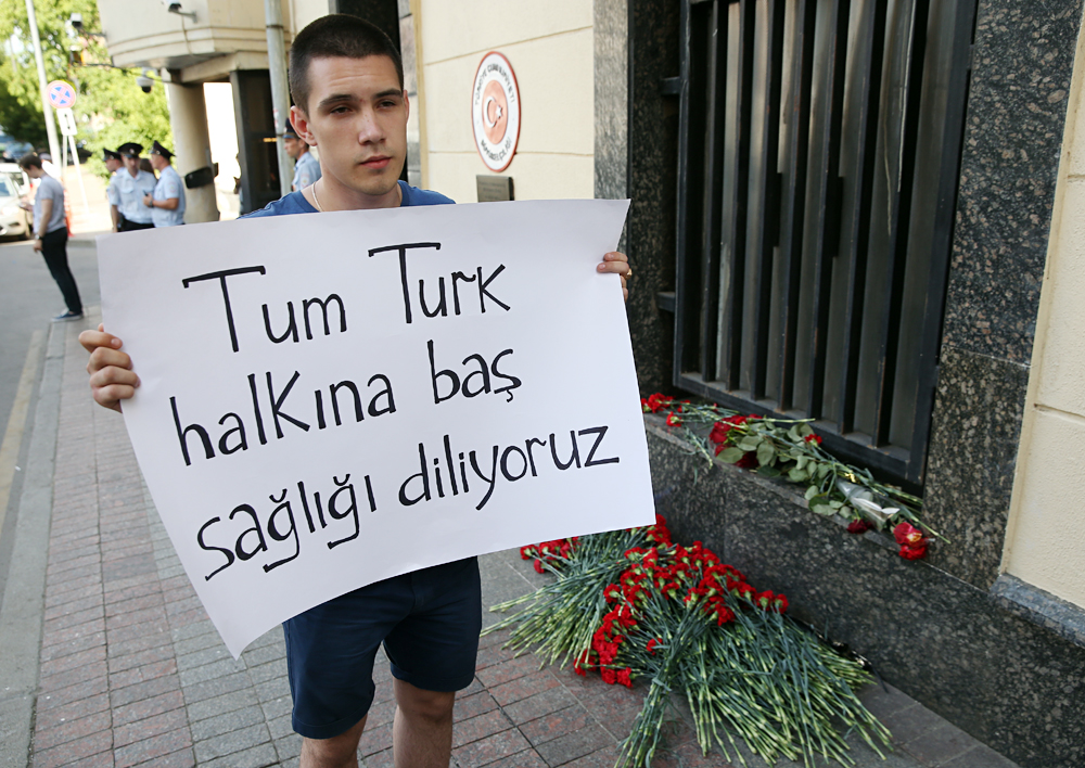 "MOSCOW, RUSSIA - JUNE 29, 2016: A man holds a sign with a message ""Tum Turk halkina bas sagligi diliyoruz"" at the entrance to the Turkish embassy in Moscow where people are laying flowers for victims of 28 June 2016 Istanbul Airport terrorist attack."
