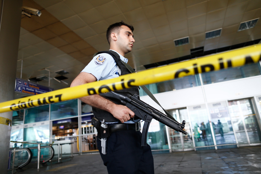 An armed Turkish policeman patrols behind a police line after multiple suicide bomb attacks at Ataturk international airport in Istanbul, June 29, 2016.