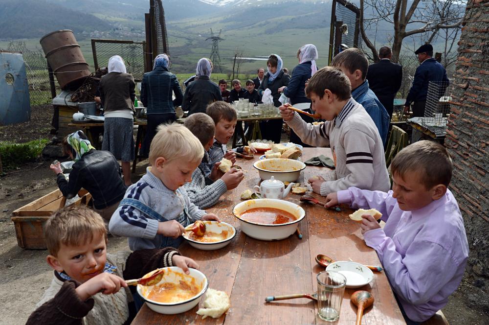Des enfants moloques lors d'un repas de commémoration après les funérailles d'un co-villageois.
