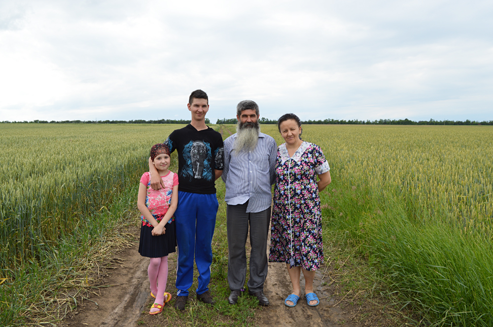 The Konovalovs, a family of Molokans, stand among their fields. Their ancestors fled from Turkey to Russia in the middle of the last century.