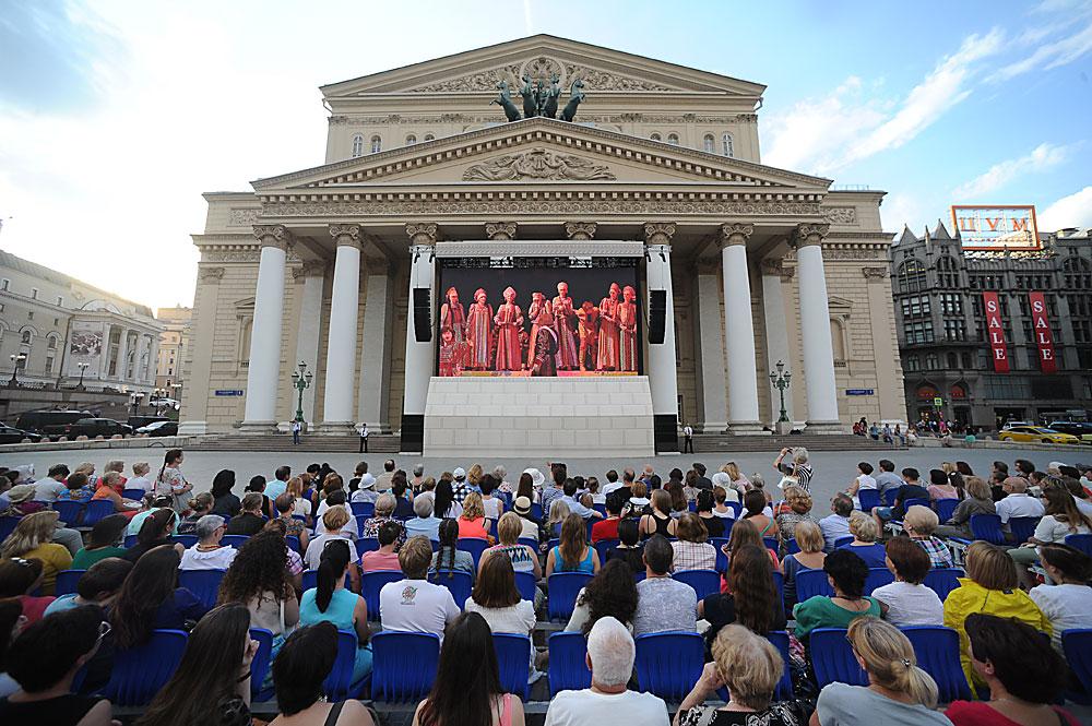 """Зрители смотрят трансляцию оперы """"Царская невеста"""" на фасаде Большого театра."""