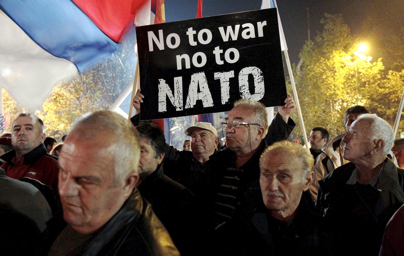 Seorang demonstran memegang papan protes dalam demonstrasi anti-NATO di Podgorica, Montenegro.
