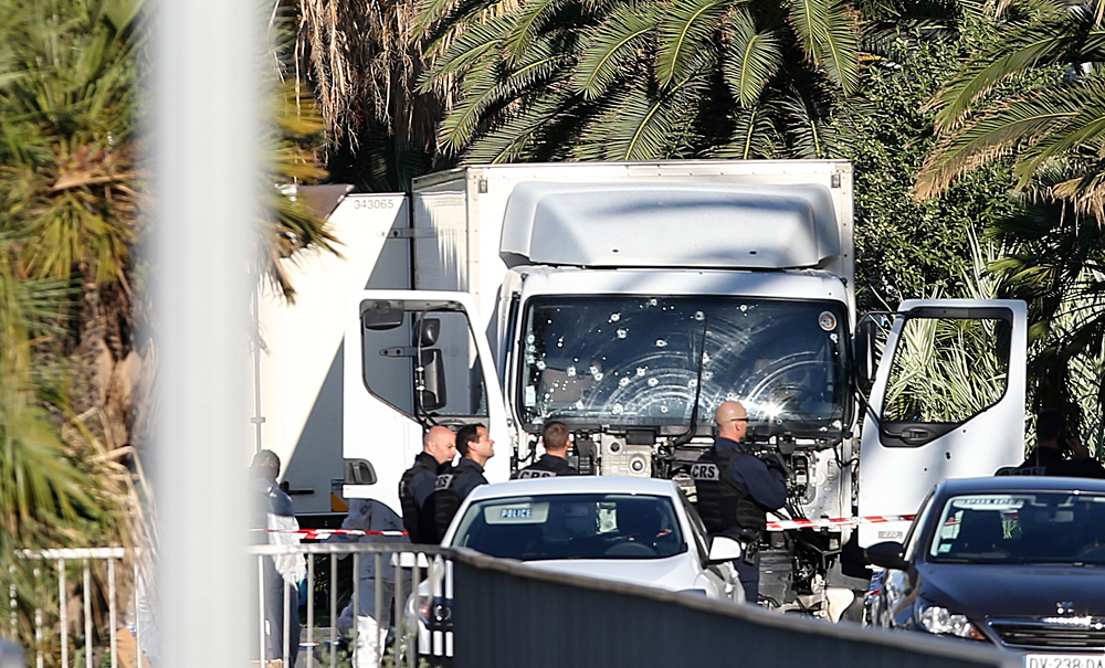The truck which slammed into revelers on July 14, is seen at the site of the attack in Nice, southern France. The large truck mowed through revelers gathered for Bastille Day fireworks in Nice, killing more than 80 people and sending people fleeing into the sea as it bore down for more than a mile along the Riviera city's famed waterfront promenade.