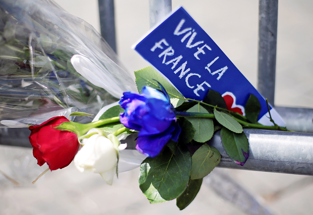 Flowers are seen attached to a fence to remember the victims of the Bastille Day truck attack in Nice in front of the French embassy in Rome, July 15, 2016.