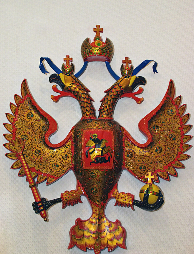 Khokhloma is a design that typically features vivid flowers and berries, with red and gold over a black background. Mostly it is used for painting wooden tableware and furniture. Why was the symbol of Russia – a two-headed eagle – colored in with khokhloma?