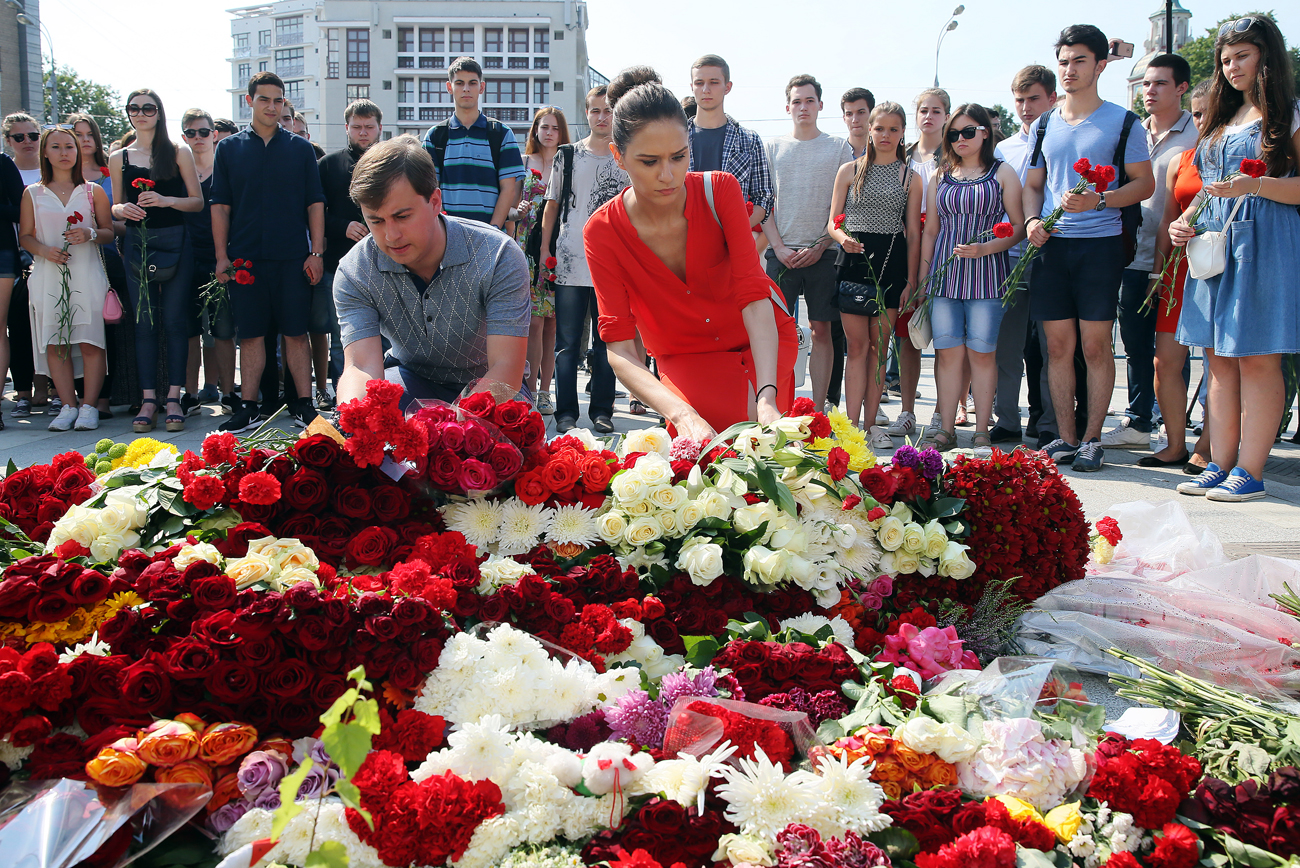 People lay flowers at the French Embassy in Moscow commemorating the victims of the 2016 terror attack in the French resort city of Nice