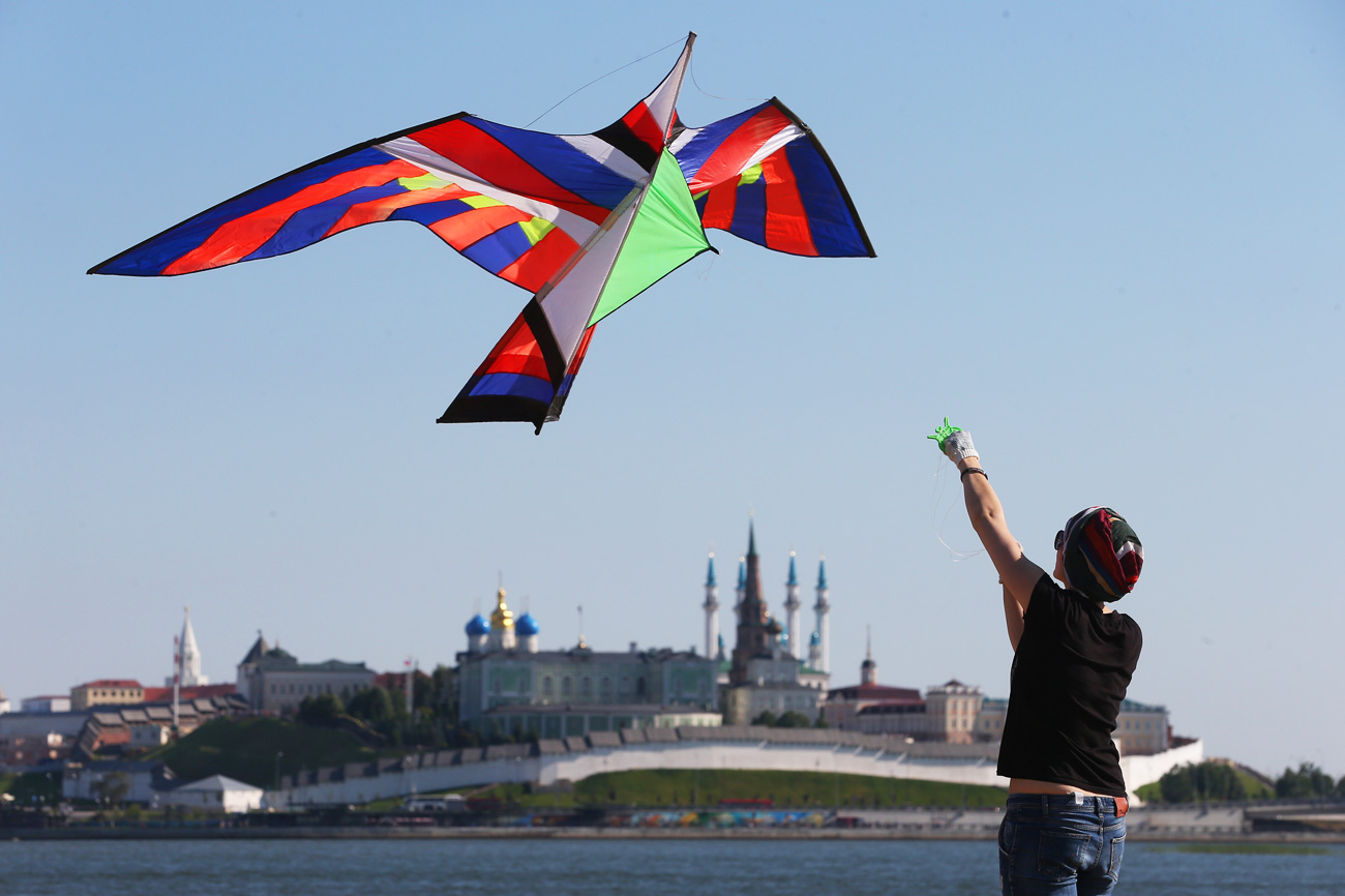 KAZAN, RUSSIA - JULY 16, 2016: A woman flying a kite takes part in the Easy to Fly kite festival.