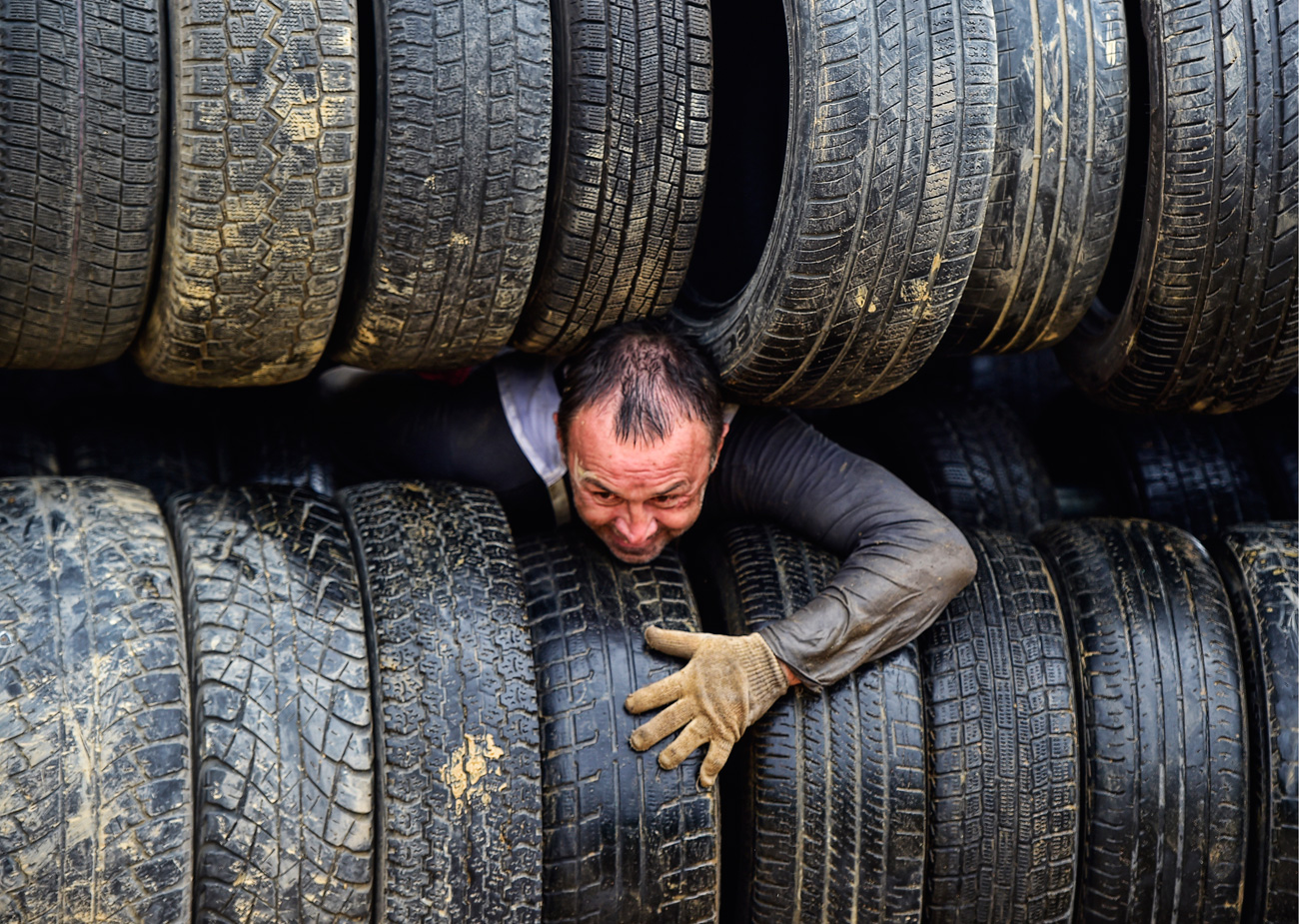 VLADIVOSTOK, RUSSIA - JULY 16, 2016: A participant crawling through tyres during a Race of Heroes obstacle course event at the Gornostai testing range.