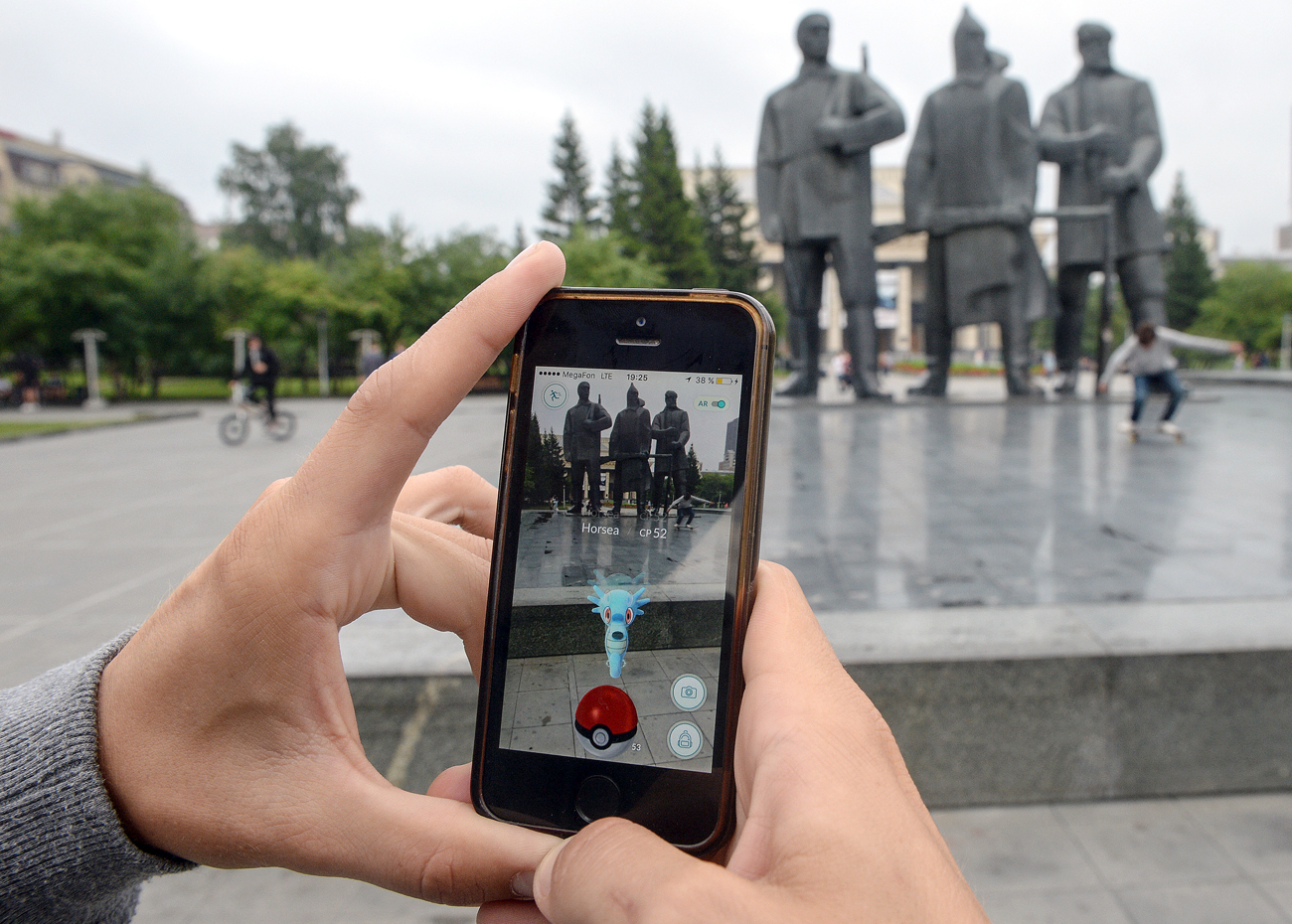 Pokémon Go, the mobile game from Nintendo, on their mobile phones in the park across the street from the Novosibirsk's Opera and Ballet Theater.