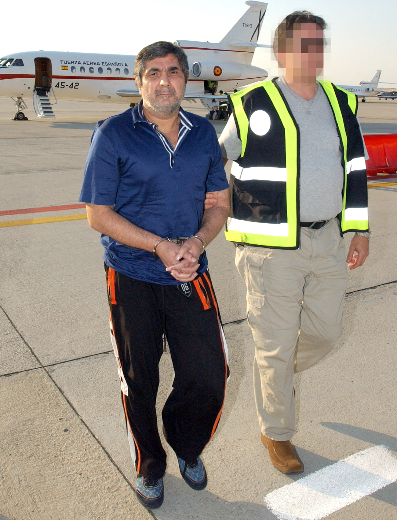 Kalashov fled Spain in 2005 after police blocked hundreds of bank accounts, seized dozens of luxury cars, and confiscated villas in a crackdown on mafias from former Soviet republics. Photo: Kalashov is escorted on arrival at the Torrejon military air base outside Madrid in June 10, 2006.