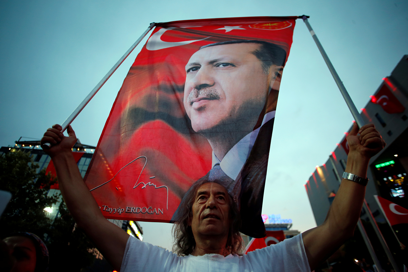 As the reports of Russia's involvement in the victory of Erdogan emerged, the Turkish president offered a different version. Photo: A supporter holds a flag depicting Turkish President during a pro-government demonstration in Ankara, July 20, 2016.