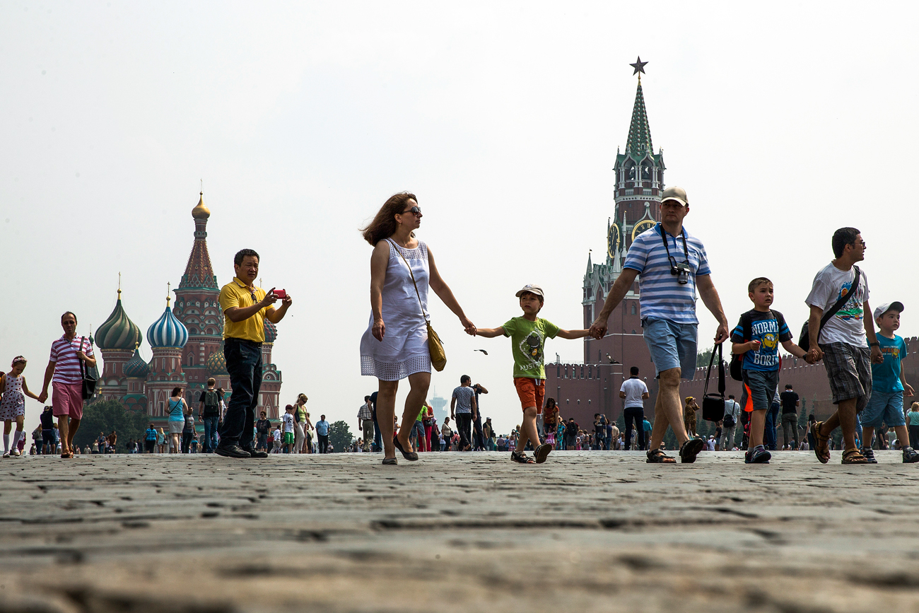 People walk through Red Square with the St. Basil's Cathedral, left, and the Spasskaya Tower, right, in the background, in Moscow.