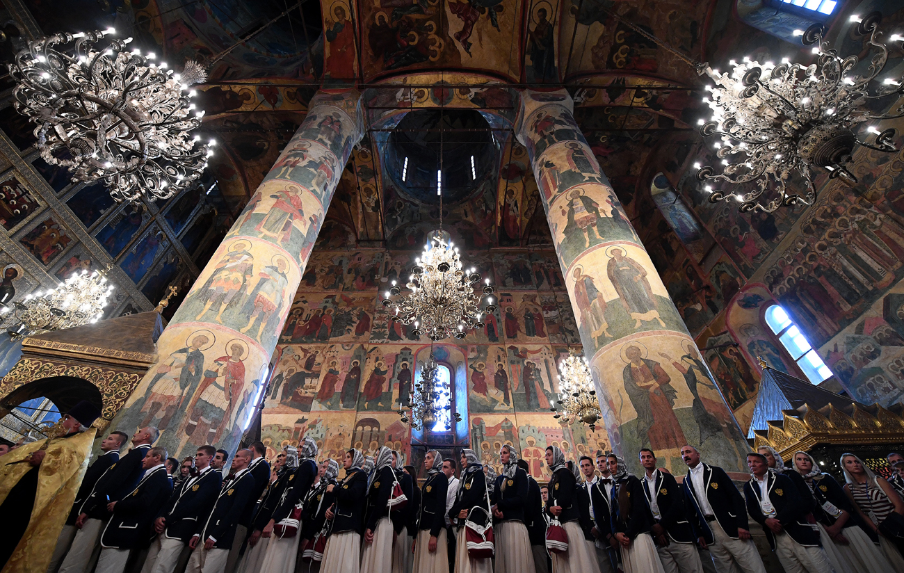 Members of Russia's Olympic team wait to receive blessings from Russian Orthodox Patriarch Kirill during a religious service at a cathedral in the Kremlin in Moscow