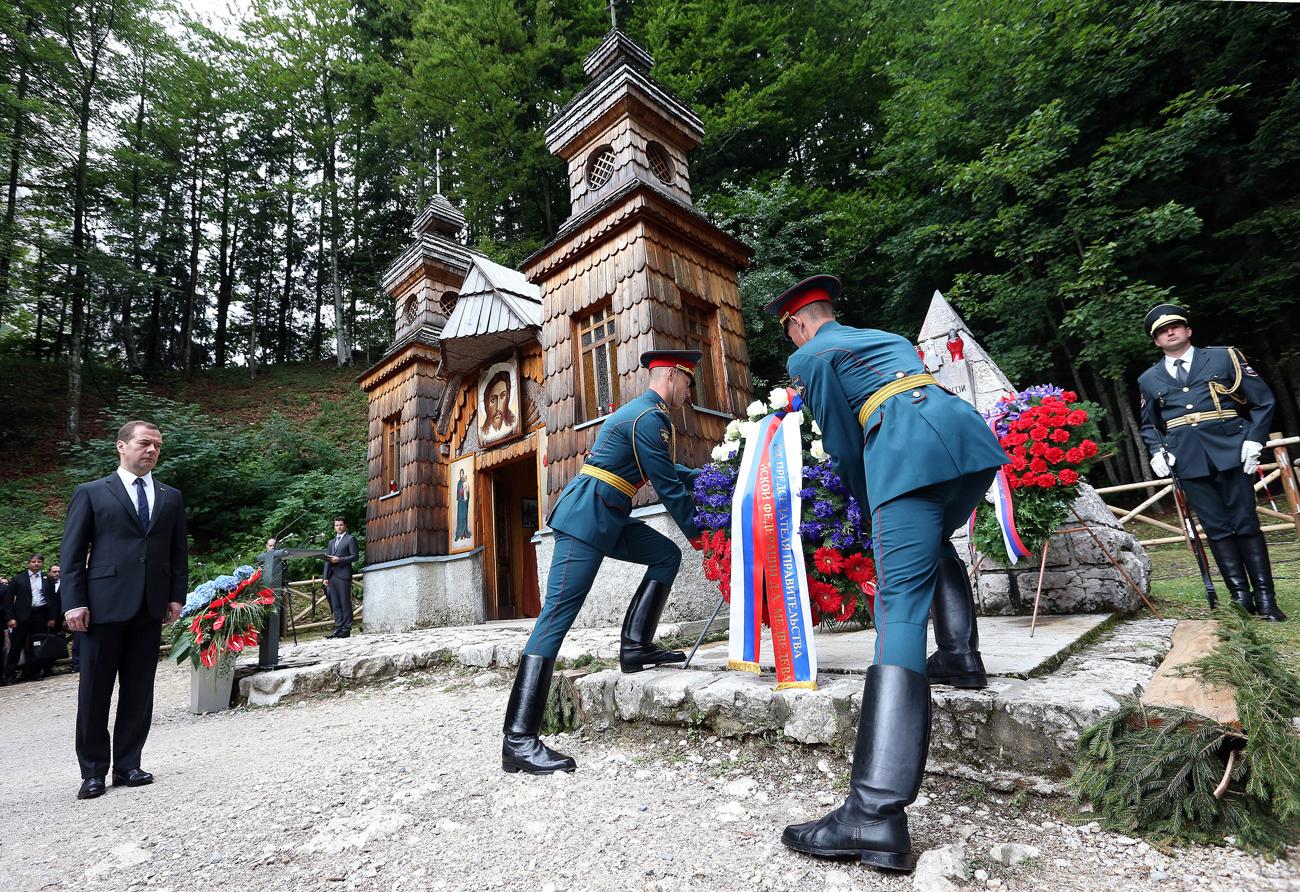 Премиерот на Русија Дмитриј Медведев (лево) полага венец на руската православна капела на преминот Вршич изградена од руските вени заробеници во текот на I Светска војна.