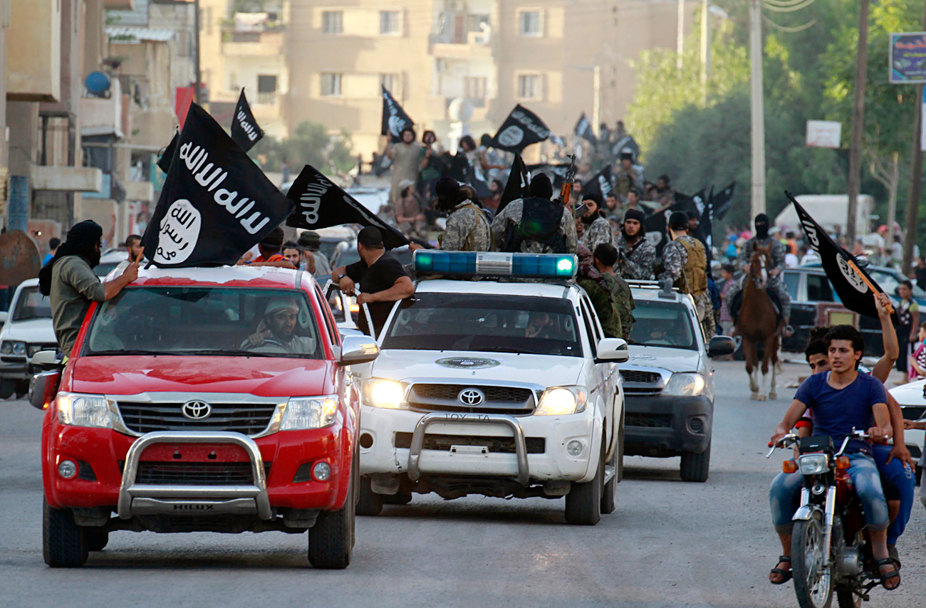 Militant Islamist fighters waving flags, travel in vehicles as they take part in a military parade along the streets of Syria's northern Raqqa province, June 30, 2014.