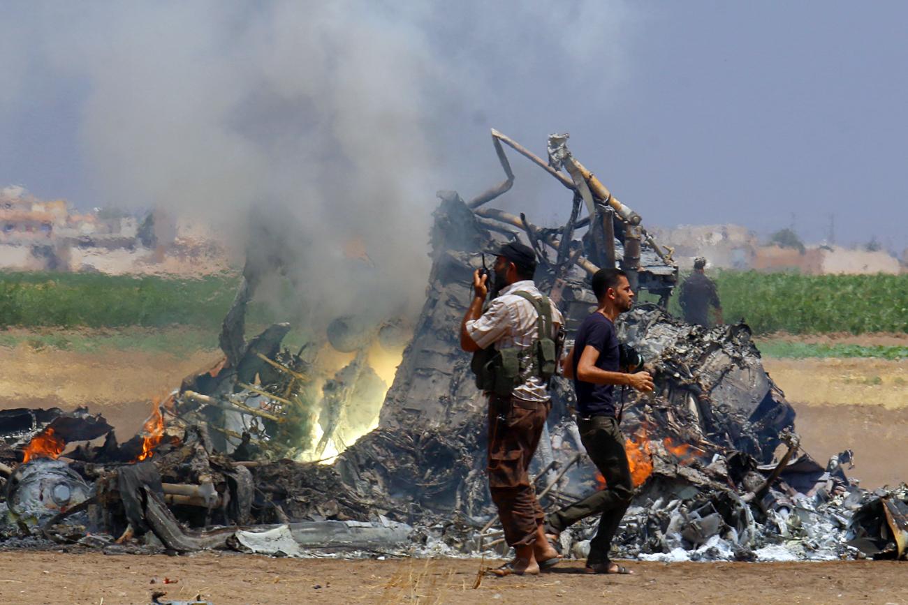 Orang-orang memeriksa puing-puing helikopter Rusia yang ditembak jatuh di sebelah utara Provinsi Idlib yang dikuasai pemberontak, 1 Agustus 2016.