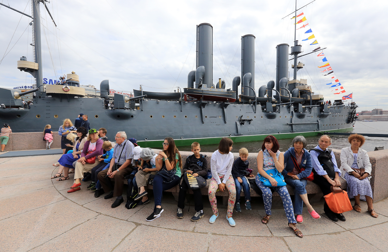 People sit in front of the Russian Aurora cruiser, Aug. 3, 2016.  Its new exhibition has been renewed during scheduled maintenance of the cruiser and is now dedicated not only to the October Revolution of 1917, but to the history of the Russian Navy.