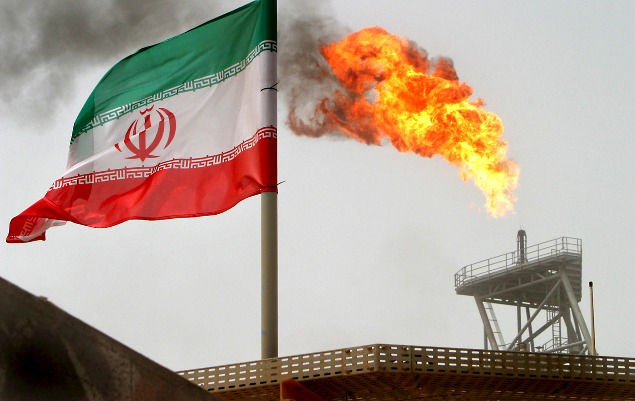 If Gazprom acquires a stake in the Iranian gas sector, it would be able to partially control Iranian gas streams and prevent competition with Russian gas in Europe. Photo: Gas flares on an oil production platform in the Soroush oil fields alongside an Iranian flag on July 25, 2005.