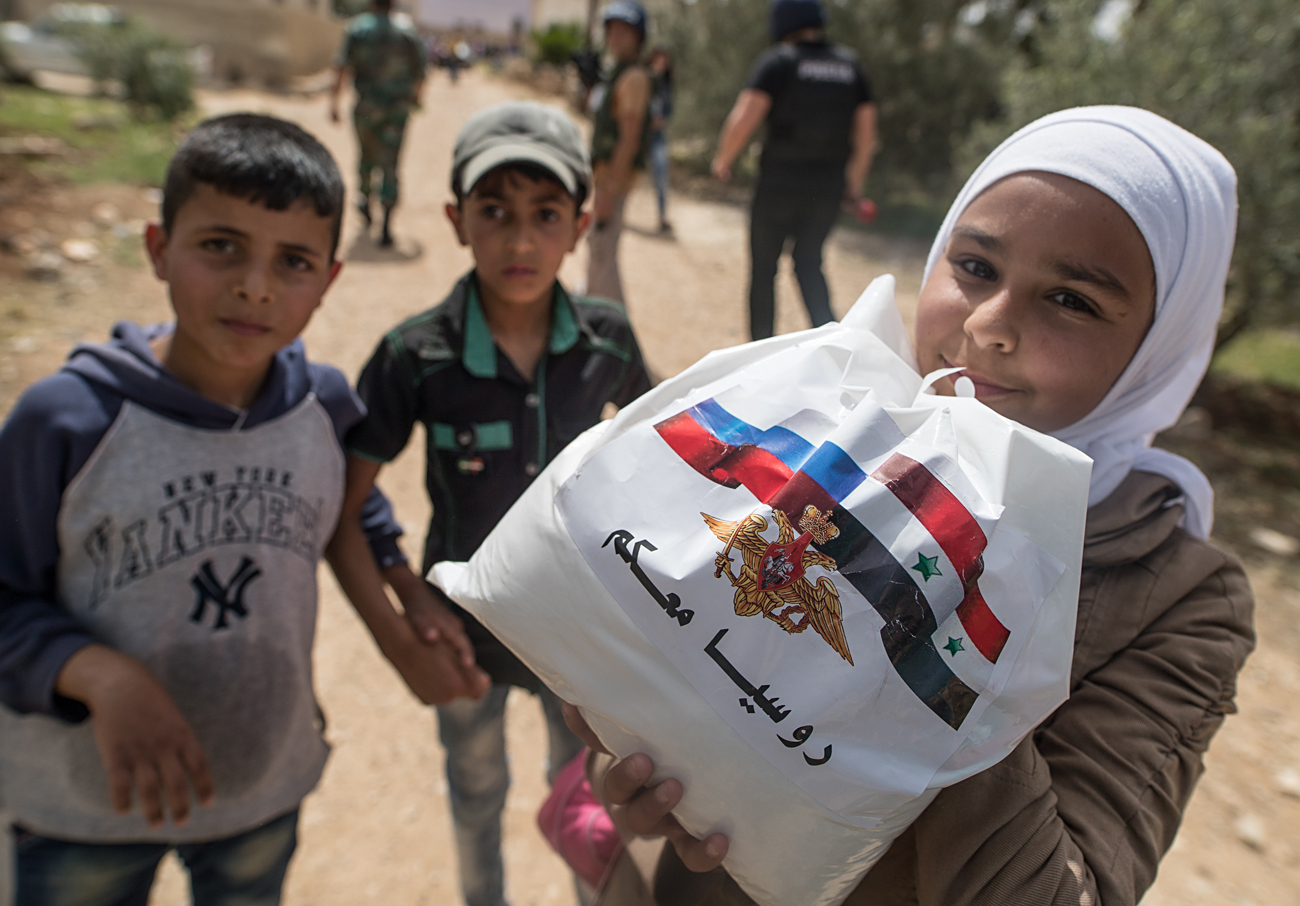 DARAA GOVERNORATE, SYRIA. Syrian children receive Russian humanitarian aid in the settlement of Alkin.