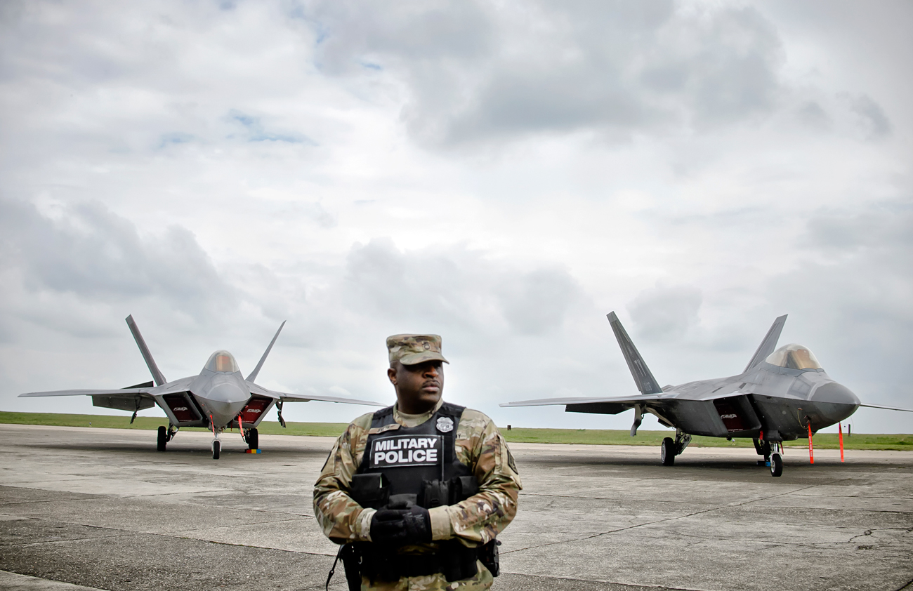 A US military policeman stands in front of U.S. Air Force F-22 Raptor fighter jets