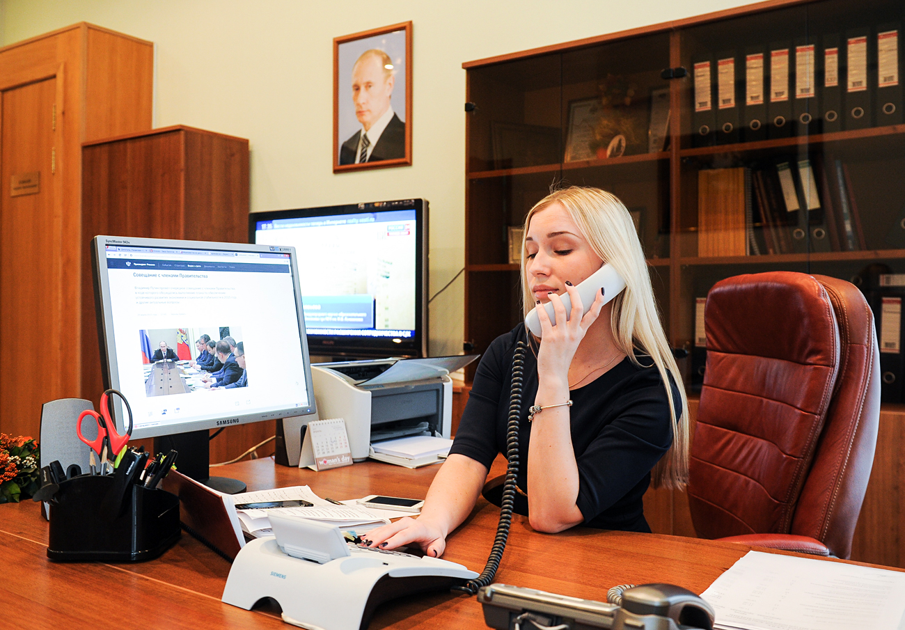 A woman works at the reception office of Ryazan City Duma chairman Andrei Kashayev. A redesigned website of the Russian president Vladimir Putin appears on the screen.