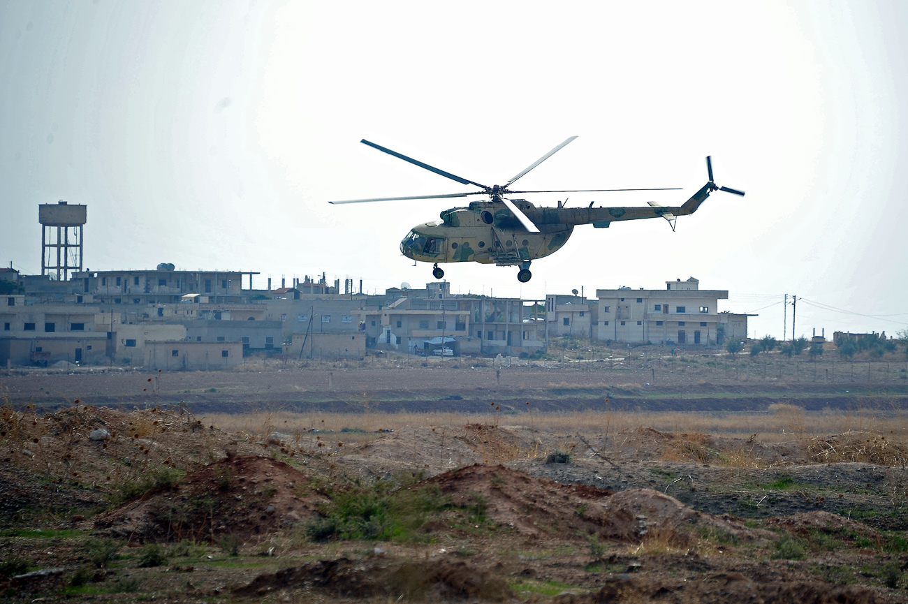A helicopter Mi-8 flies over the Hama airbase near the city of Hama, Syria's Hama Province.