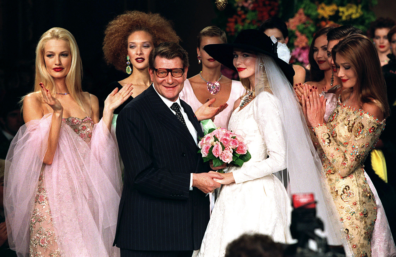 French fashion designer Yves Saint Laurent holds the hands of German model Claudia Schiffer as Dutch model Karen Mulder (left) and Italian Carla Bruni (right) and other models behind, applaud following his Autumn/Winter 1996 high fashion collection, July 10, 1996.