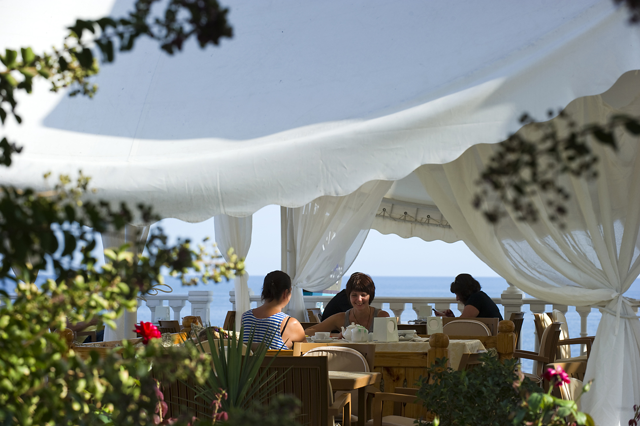 Holidaymakers at a cafe of the Relax Center Irei hotel in Semidvorye near Alushta, Crimea.