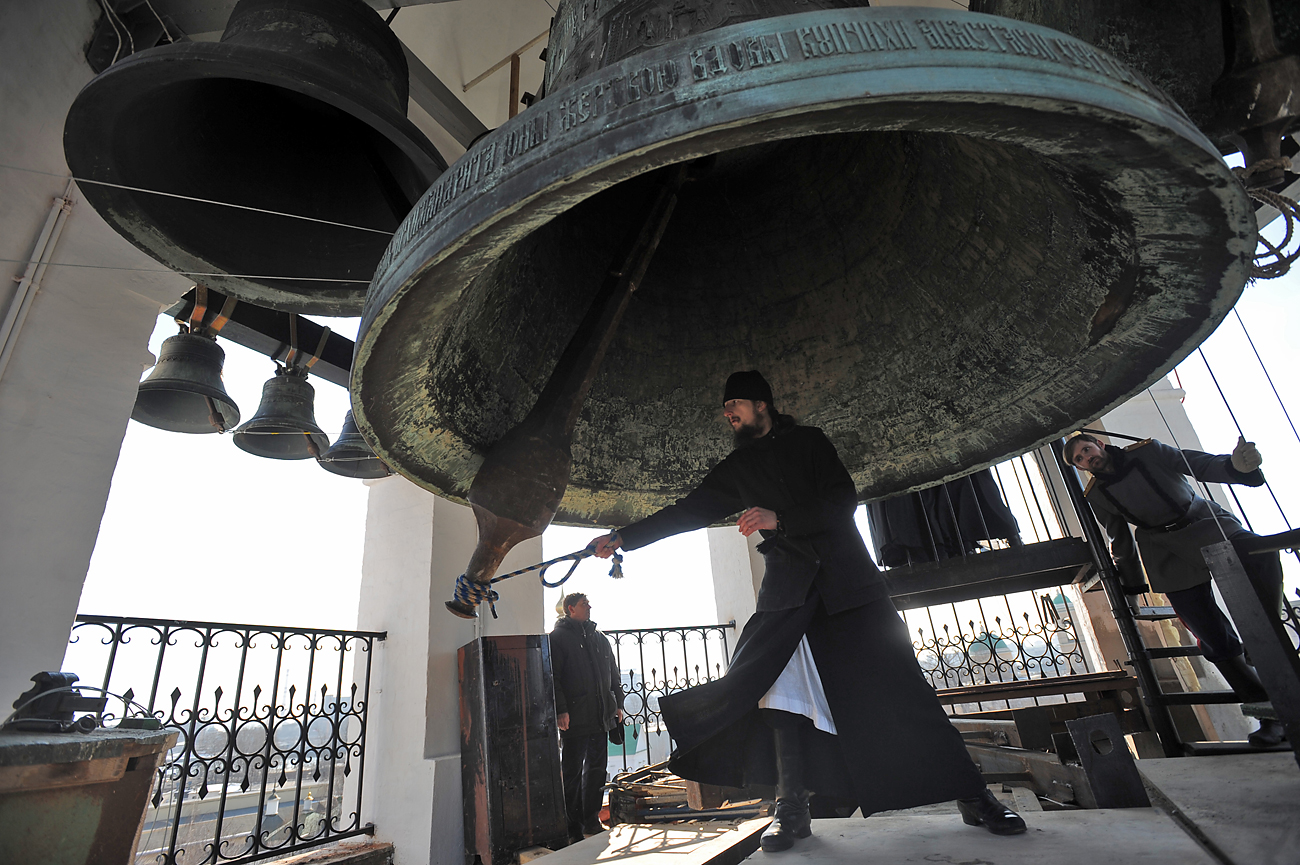 Orthodox priest rings the Bolshoi Bell, aka the Everyday Bell (the largest of the so-called Harvard Bells, the Big One) on top of the Church of St. Simeon Stylites at Moscow's Svyato-Danilov Monastery.